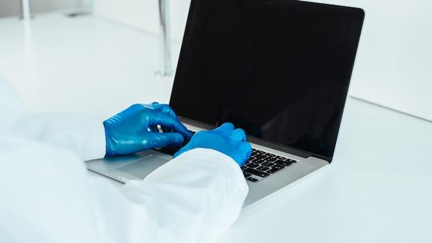 Nahansicht. arzt in schutzhandschuhen, der auf einem laptop tippt. das konzept der telemedizin.