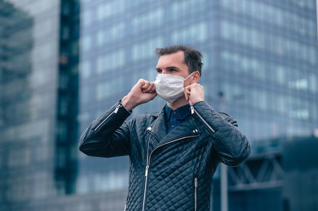 Nahansicht. attraktiver mann, der eine schutzmaske auf einer stadtstraße aufsetzt. konzept des gesundheitsschutzes