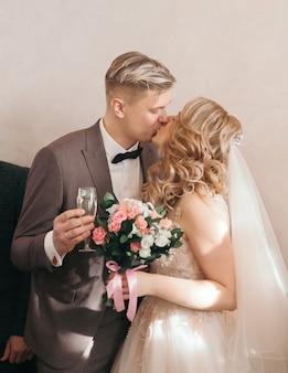 Nahansicht. braut und bräutigam mit gläsern champagner küssen sich. feiertage und veranstaltungen.