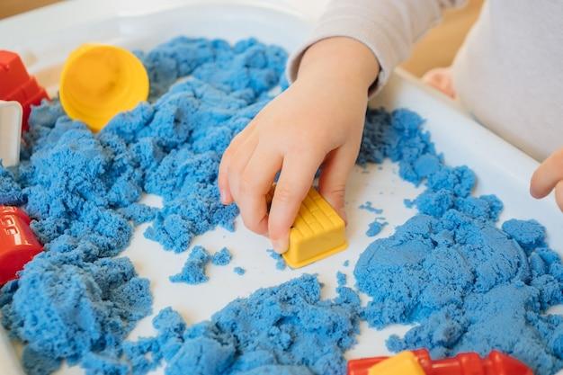 Nahansicht der kinderhände, die mit kinetischem sand spielen. kreatives spiel für kinder für frühe entwicklung und feinmotorik.