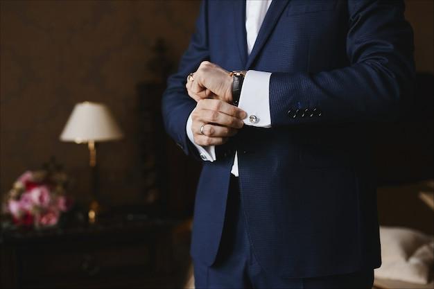 Nahansicht der luxusuhren auf der hand eines geschäftsmannes in einem anzug und in einem hemd mit manschettenknöpfen.