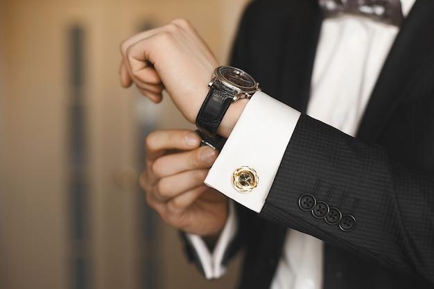 Nahansicht der luxusuhren auf der hand eines geschäftsmannes in einem smoking und einem hemd mit manschettenknöpfen.