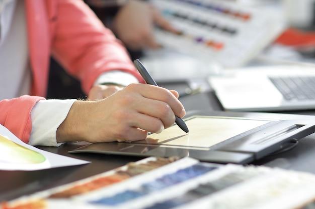 Nahansicht. ein grafikdesigner verwendet ein grafiktablett am schreibtisch