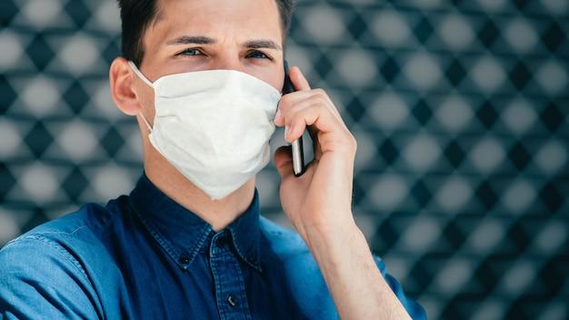 Nahansicht. ein junger mann in einer schutzmaske, der in die kamera schaut. foto mit einem kopierraum