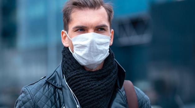 Nahansicht. ein mann in einer schutzmaske auf dem hintergrund einer stadtstraße. foto mit einem kopierraum