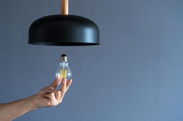 Nahansicht. eine hand wechselt eine glühbirne in einer stilvollen loftlampe. spiralfadenlampe. moderne inneneinrichtung.
