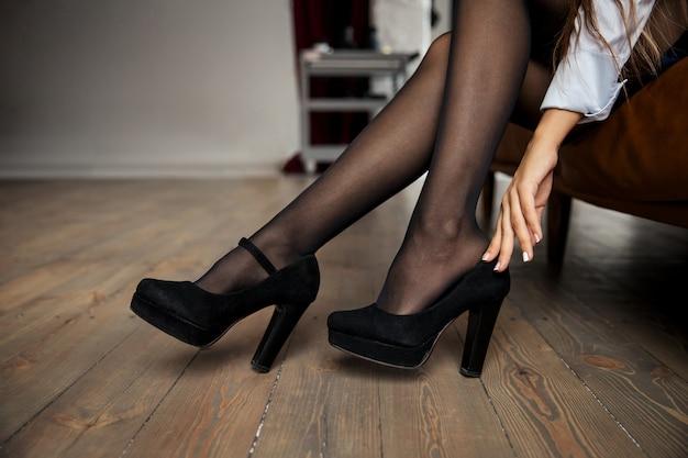 Nahansicht. elegante geschäftsfrau zieht ihre schuhe aus und ruht sich nach der arbeit zu hause aus. hochwertiges foto
