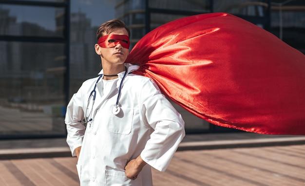 Nahansicht. ernsthafter arzt in einem superheldenkap, das auf einer stadtstraße steht