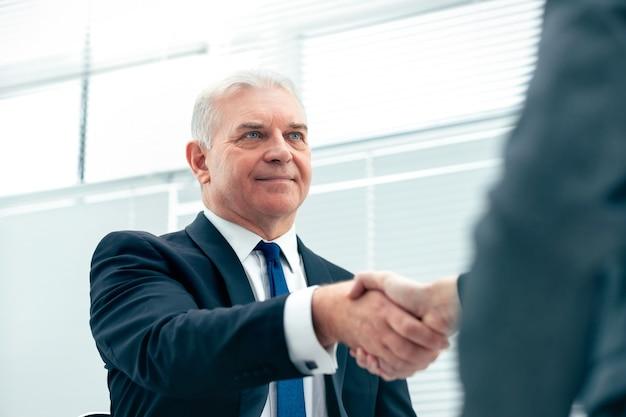 Nahansicht. fester geschäftshandschlag auf einem verschwommenen bürohintergrund. konzept der partnerschaft