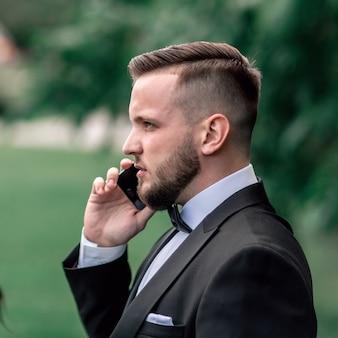 Nahansicht. geschäftsmann spricht auf seinem smartphone. foto mit kopierraum