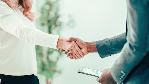 Nahansicht. geschäftsmann und geschäftsfrau bestätigen den vertrag mit einem handschlag. konzept der partnerschaft