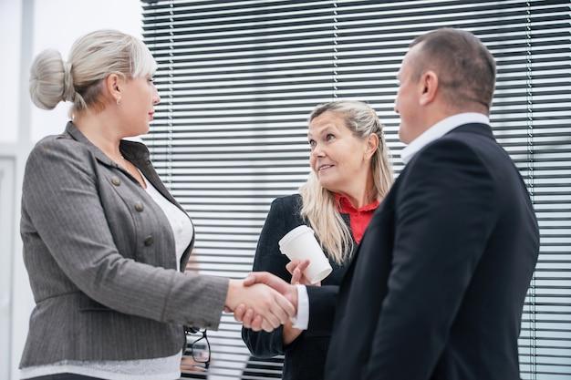 Nahansicht. geschäftspartner, die sich bei einem bürotreffen die hand geben. unternehmenskonzept