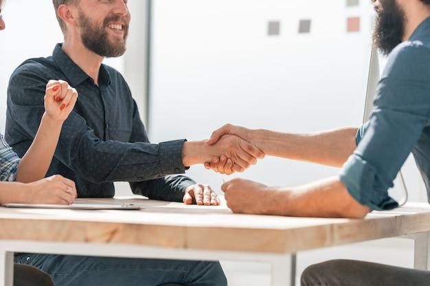Nahansicht. glückliche geschäftspartner händeschütteln. foto mit einer kopie des raumes.