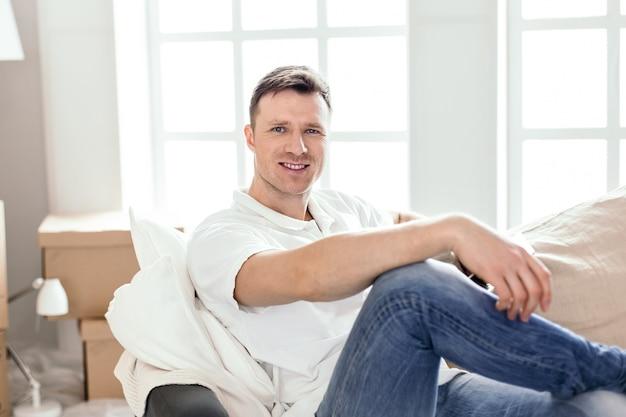 Nahansicht. glücklicher mann, der auf der couch in seiner neuen wohnung sitzt