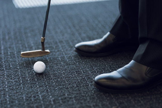 Nahansicht. golfclub und golfball auf einem grauen teppich.
