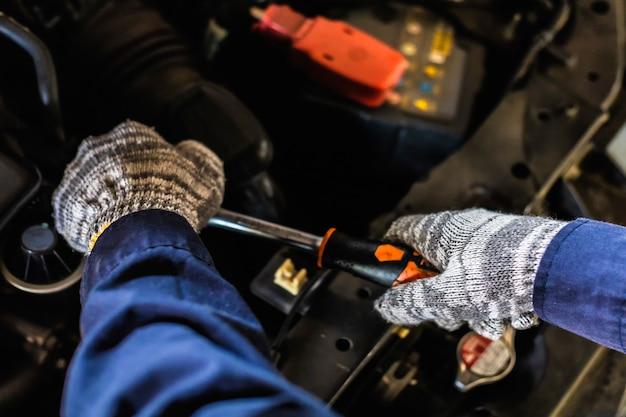 Nahansicht. hand hält einen schraubenschlüssel und einen schraubendreher, die in einer autowerkstatt für servicereparaturen arbeiten.