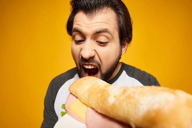 Nahansicht. hübscher bärtiger mann beißt großes sandwich.