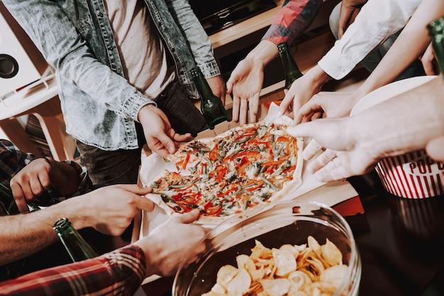 Nahansicht. junge firma, die pizza auf party isst.