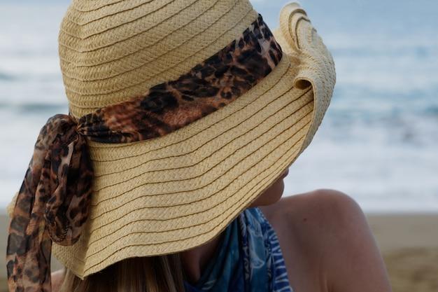 Nahansicht. junge frau, die am strand sitzt, frau im hut, der ozean betrachtet.