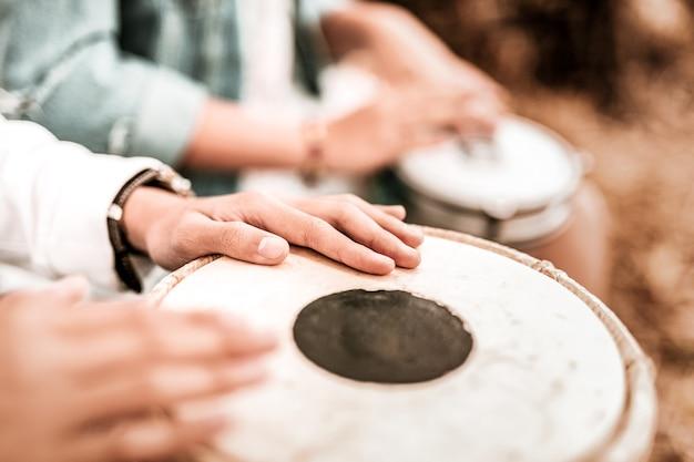 Nahansicht. junger hippie, der musik macht, während er wochenende im park verbringt