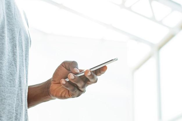 Nahansicht. junger mann, der auf den bildschirm seines smartphones schaut. foto mit kopierraum