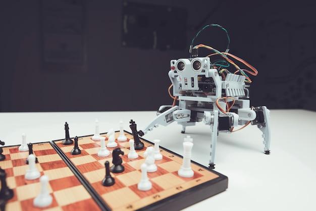 Nahansicht. kleiner grauer roboter, der schach auf tabelle spielt.