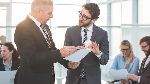 Nahansicht. leiter und assistent diskutieren ein arbeitsdokument. büroarbeitstage