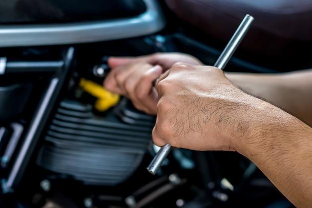 Nahansicht. leute, die hand halten, reparieren ein motorrad verwenden sie einen schlüssel und einen schraubenzieher