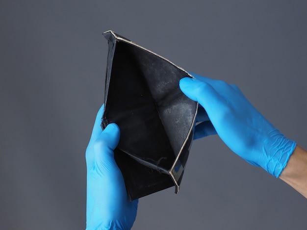 Nahansicht. mann in blauen handschuhen hält leere brieftasche.