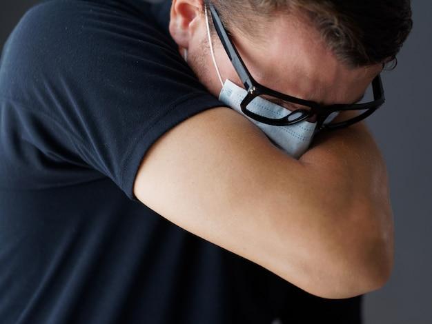 Nahansicht. mann in der medizinischen maske hustet in seinem ellbogen. richtiges niesen.