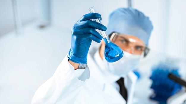 Nahansicht. medizinische flasche in den händen des forschers. wissenschaft und gesundheit.
