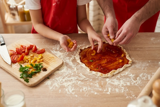 Nahansicht. pizza, die mit gemüsescheiben sich vorbereitet.