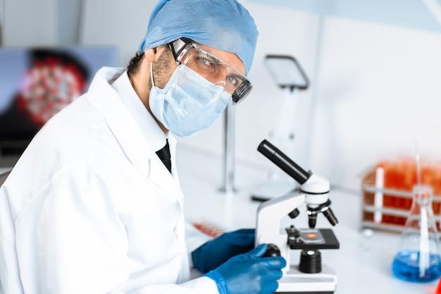 Nahansicht. talentierter wissenschaftler, der an einem tisch im labor sitzt.