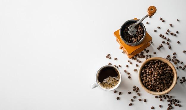 Nahansicht von kaffeebohnen mit kaffeetasse und mühle
