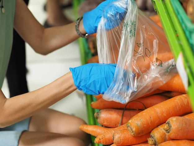 Nahansicht. weibliche hände in blauen handschuhen, die eine karotte im supermarkt während des pandemischen coronavirus covid-19 wählen.