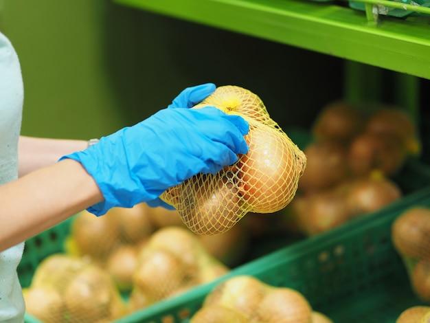 Nahansicht. weibliche hände in blauen handschuhen, die eine zwiebel im supermarkt während des pandemischen coronavirus covid-19 wählen.