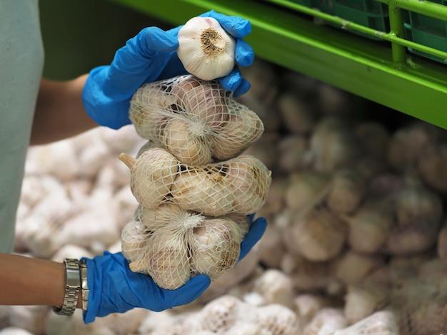 Nahansicht. weibliche hände in blauen handschuhen nehmen einen knoblauch im supermarkt während der pandemie coronavirus covid-19.