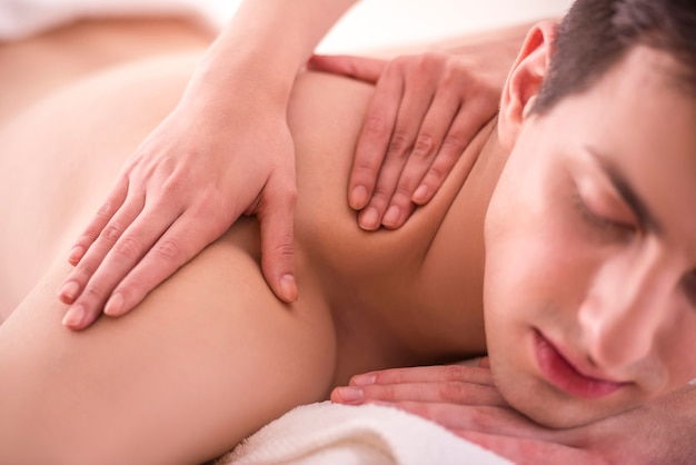 Nahansicht. weiblicher masseur, der massage auf mann im badekurortsalon tut.