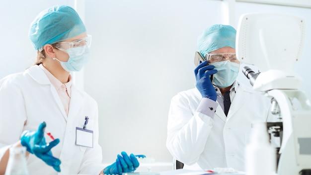 Nahansicht. wissenschaftler in einer schutzmaske sprechen auf einem handy.