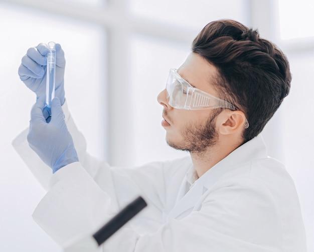 Nahansicht. wissenschaftler mit einem medizinischen schlauch, der im labor steht. wissenschaft und gesundheit