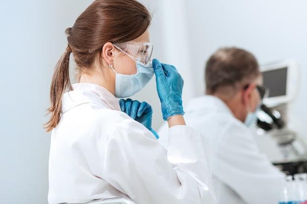 Nahansicht. wissenschaftlerin sitzt an einem labortisch. foto mit einem exemplarplatz.