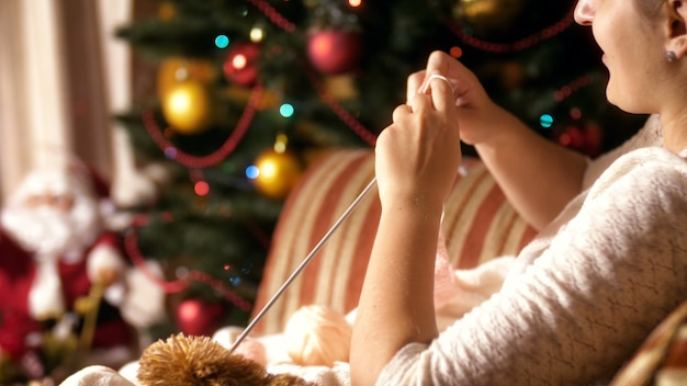 Nahaufnahme 4k aufnahmen einer jungen frau, die im sessel neben einem leuchtenden weihnachtsbaum sitzt und einen wollpullover für ihre kinder strickt. menschen entspannen im winterurlaub und feiern zu hause