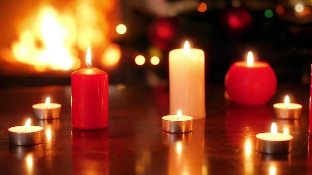 Nahaufnahme 4k aufnahmen von brennenden kerzen gegen feuer im kamin und leuchtenden weihnachtsbaum. perfekter hintergrund oder kulisse für weihnachten oder neujahr
