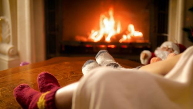 Nahaufnahme 4k-aufnahmen von der familie, die unter der decke liegt und warme wollsocken trägt, die sich am feuer im kamin erwärmen. menschen entspannen im winterurlaub und feiern zu hause