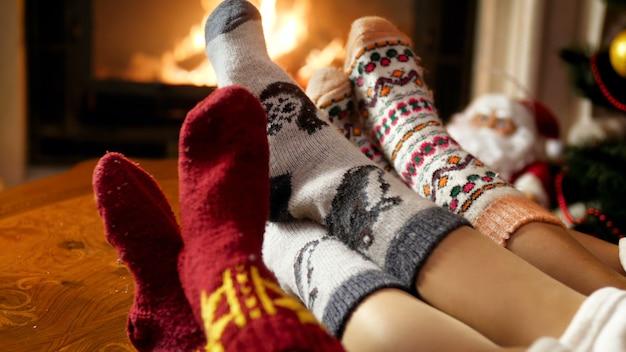 Nahaufnahme 4k-aufnahmen von drei paar füßen, die warme wollsocken tragen, die sich im wohnzimmer am brennenden kamin erwärmen. menschen entspannen im winterurlaub und feiern zu hause