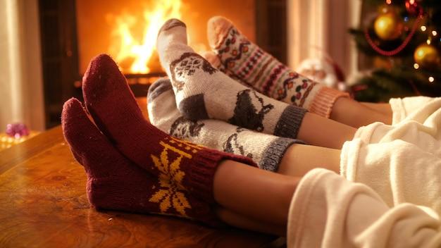 Nahaufnahme 4k-aufnahmen von menschen in wollsocken, die nachts füße neben brennendem feuer im kamin halten. menschen entspannen im winterurlaub und feiern zu hause