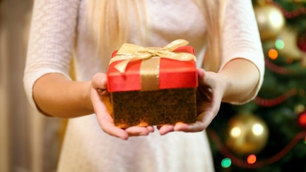 Nahaufnahme 4k filmmaterial einer jungen frau, die eine rote kiste mit geschenken und geschenken zu weihnachten vom weihnachtsmann hält. familie, die an winterferien und -feiern geschenke gibt und empfängt.