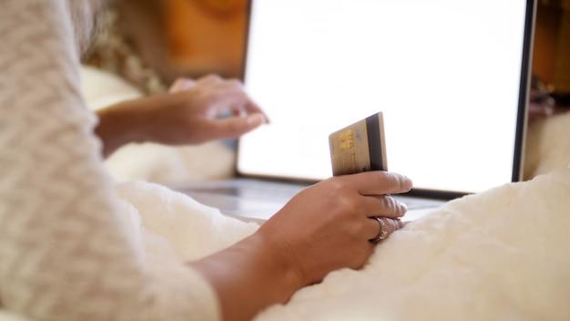 Nahaufnahme 4k filmmaterial einer jungen frau, die kreditkarte in der hand hält, während sie im intrnet und in online-shops surft. konzeptaufnahme von online-shopping und e-commerce.