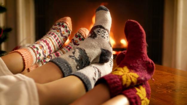 Nahaufnahme 4k filmmaterial von familie mit wollsocken, die füße neben feuer im kamin halten. menschen entspannen im winterurlaub und feiern zu hause