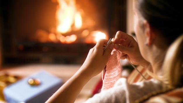 Nahaufnahme 4k filmmaterial von frau strickte wollschal für ihre kinder, während sie neben dem brennenden kamin im haus saß. menschen entspannen im winterurlaub und feiern zu hause
